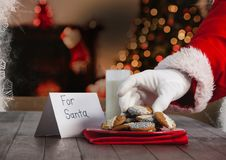 Santa claus putting Christmas cookies on table. Hand of santa claus putting Christmas cookies on table Royalty Free Stock Photography