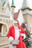 Santa Claus Putting Gift In Bag fuera de la casa Imágenes de archivo libres de regalías