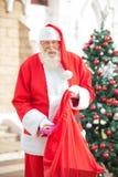 Santa Claus Putting Gift In Bag Royalty Free Stock Photo