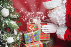 Santa Claus putting gift box or present under Christmas tree Stock Photo