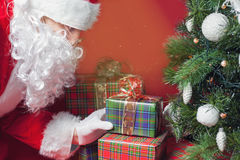 Santa Claus putting gift box or present under Christmas tree Royalty Free Stock Images