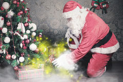 Santa Claus putting gift box or present under Christmas tree Stock Photos