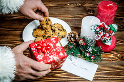 Santa Claus putting gift and takes a cookie left for him treats. Royalty Free Stock Photo