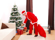 Santa Claus putting gift under christmas tree. Senior man in Santa Claus uniform, putting a gift from bag under the decorated christmas tree Stock Photo