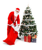 Santa Claus putting gifts under christmas tree. Senior man wearing Santa Claus uniform, taking out gifts from bag and putting under the decorated christmas tree Royalty Free Stock Image