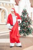 Santa Claus Putting Present In Bag Stock Photo