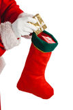 Santa claus putting presents in christmas stockings Royalty Free Stock Image