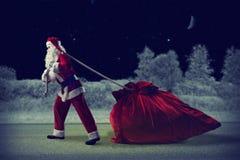 Santa Claus puxa um saco enorme dos presentes Foto de Stock Royalty Free