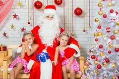 Santa Claus que abraza a dos hermanas de las muchachas Foto de archivo