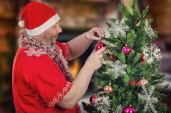 Santa Claus que adorna el árbol de navidad con las bolas Foto de archivo