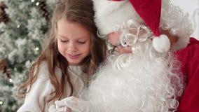 Santa Claus que amarra uma curva da fita em um presente para uma menina que senta-se perto da árvore de Natal em casa filme