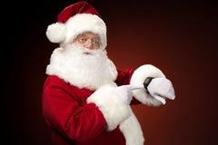Santa Claus que aponta no Smart-relógio fotos de stock royalty free