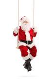 Santa Claus que balancea en un oscilación de madera Imagenes de archivo