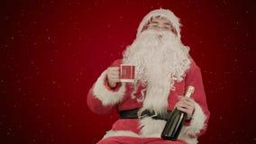 Santa Claus que celebra el champán en fondo rojo con nieve Foto de archivo