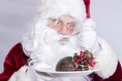 Santa Claus que come un pudín de la Navidad Imagen de archivo libre de regalías