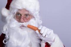 Santa Claus que come una zanahoria Foto de archivo