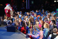 Santa Claus que cuenta historias a un grupo de niños Noche de la Navidad Santa Claus en etapa Fotos de archivo