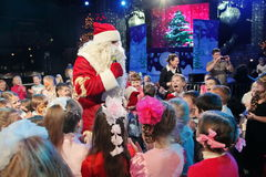 Santa Claus que cuenta historias a un grupo de niños Noche de la Navidad Santa Claus en etapa Fotos de archivo libres de regalías