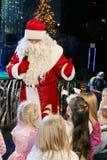 Santa Claus que cuenta historias a un grupo de niños Noche de la Navidad Santa Claus en etapa Imagen de archivo libre de regalías