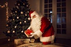 Santa Claus que deixa um presente sob a árvore de Natal imagens de stock