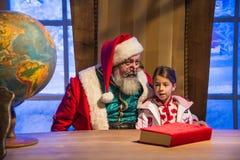 Santa Claus que detiene a una niña en sus brazos delante de su de Fotografía de archivo libre de regalías