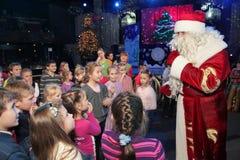 Santa Claus que diz histórias a um grupo de crianças Noite de Natal Santa Claus na fase Imagem de Stock