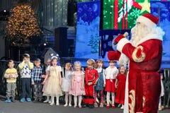 Santa Claus que diz histórias a um grupo de crianças Noite de Natal Santa Claus na fase Fotos de Stock