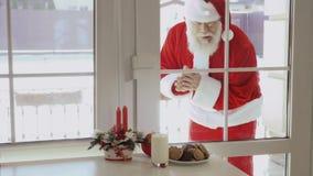 Santa Claus que golpea en ventana y quiere probar la leche y las galletas almacen de metraje de vídeo