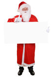 Santa Claus que guarda os polegares vazios do sinal acima em bom super do Natal Imagem de Stock Royalty Free