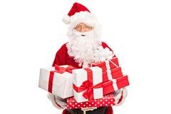 Santa Claus que guarda um grupo dos presentes imagens de stock