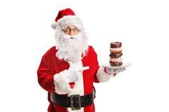 Santa Claus que guarda uma placa dos anéis de espuma e de apontar fotos de stock
