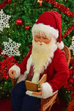 Santa Claus que lê um livro na frente da árvore de Natal Fotos de Stock Royalty Free