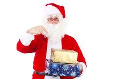 Santa Claus que le muestra los regalos hermosos Foto de archivo