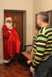 Santa Claus que leva um saco dos presentes e do seu pessoal foi ao apartamento cumprimenta o homem, menino Imagens de Stock