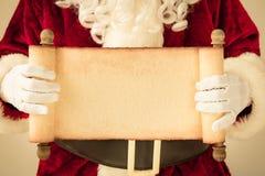 Santa Claus que lleva a cabo el espacio en blanco de papel de la voluta Imagen de archivo libre de regalías