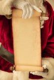 Santa Claus que lleva a cabo el espacio en blanco de papel de la voluta Imagenes de archivo