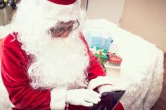 Santa Claus que lleva a cabo jugar la tableta foto de archivo