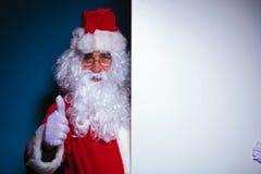 Santa Claus que lleva a cabo a un tablero en blanco a su izquierda Foto de archivo