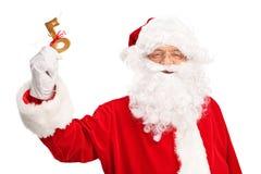 Santa Claus que lleva a cabo una llave envuelta con la cinta roja Imágenes de archivo libres de regalías