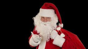 Santa Claus que lleva su bolso, miradas en la cámara envía un beso y una onda, negro, cantidad común del soplo almacen de metraje de vídeo