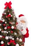 Santa Claus que oculta detrás de un árbol de navidad Imágenes de archivo libres de regalías
