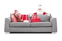 Santa Claus que oculta detrás de un sofá por completo de presentes Foto de archivo libre de regalías