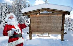 Santa Claus que señala en muestra en blanco Imagenes de archivo