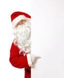 Santa Claus que señala en una bandera en blanco Imagenes de archivo