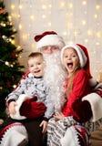 Santa Claus que se sienta con los niños lindos muchacho y muchacha de los niños felices cerca del árbol de navidad Imagen de archivo