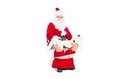 Santa Claus que se sienta en un retrete y que sostiene el papel higiénico Foto de archivo