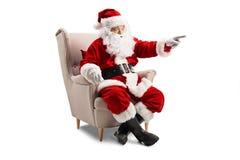 Santa Claus que senta-se em uma poltrona e em apontar foto de stock