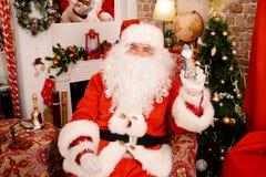 Santa Claus que sostiene la estatuilla de la Navidad imagen de archivo