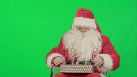 Santa Claus que sostiene los regalos de la Navidad en un verde almacen de metraje de vídeo