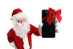 Santa Claus que sostiene un teléfono con una cinta roja fotografía de archivo libre de regalías